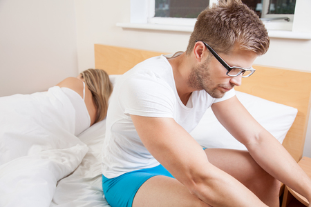 Unhappy young couple with problems in bedroom photo