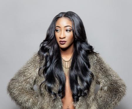 manteau de fourrure: Belle jeune femme noire avec une élégante cheveux bouclés Banque d'images