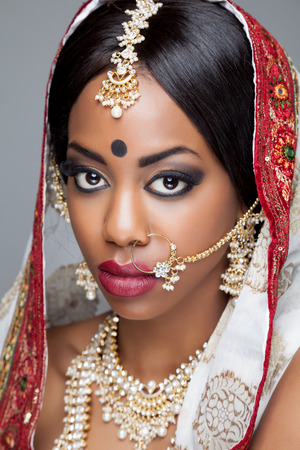 bridal makeup: Young Indian woman dressed in traditional clothing with bridal makeup and jewelry