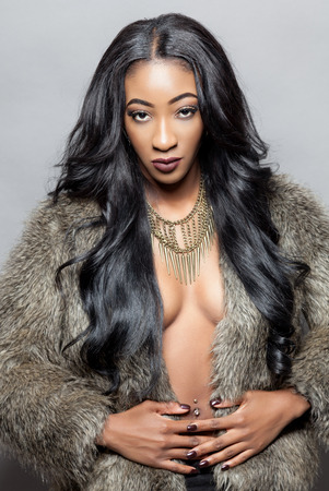 Beautiful black woman with long curly hair wearing a fur coat