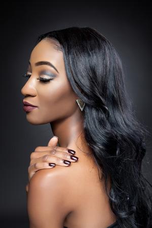lang haar: Jonge zwarte schoonheid met elegante lang krullend haar Stockfoto