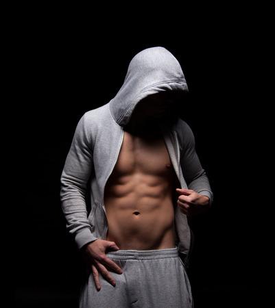 torso nudo: Corpo muscoloso di un uomo che indossa una felpa e cappuccio