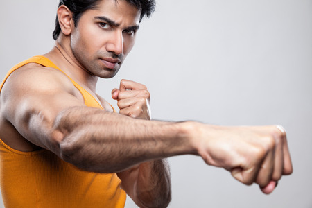 Handsome Indian man giving a knockout punch photo