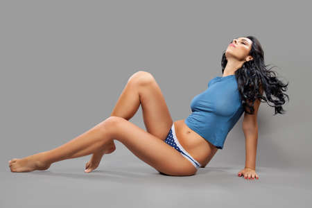 Young woman with perfect body sitting on the floor photo