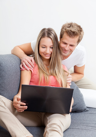 Happy couple shopping online from the comfort of their home photo