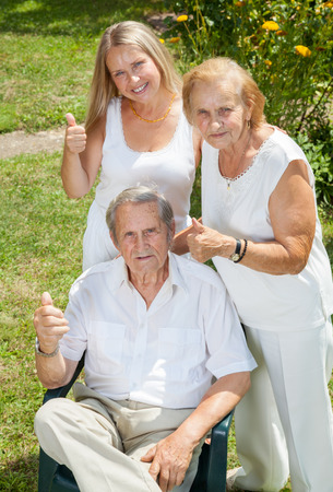 Elderly couple and their daughter outdoors photo