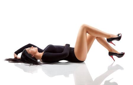 tacones negros: Mujer joven con un cuerpo impresionante acostado en el piso