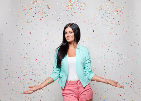 Young beautiful woman in party mood with confetti all around photo