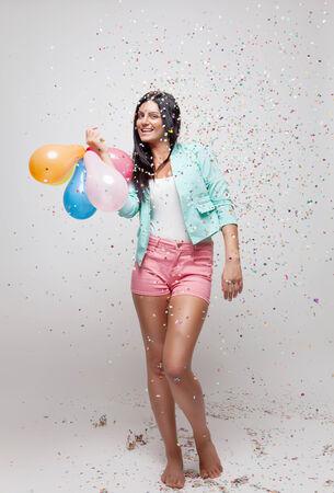 personas festejando: Mujer hermosa joven en ambiente de fiesta con confeti a su alrededor