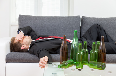 hangover: Depressed businessman drunk at home with empty bottles on table