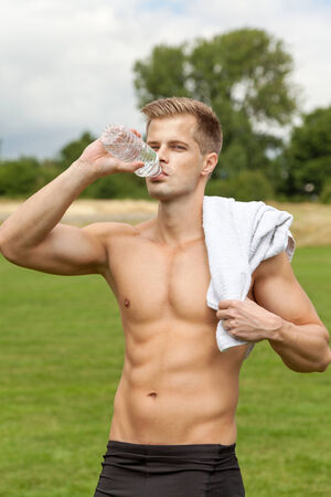 man drinking water: Muscular young man drinking water after excercise