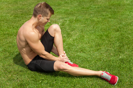 Man holding his ankle after injury during excercise photo