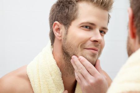 バスルームの鏡にハンサムな無精ひげを生やした男