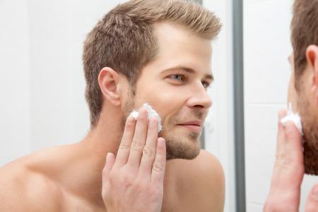 espejo: Hombre sin afeitar hermoso que mira en el espejo en el baño