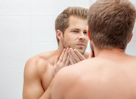 body grooming: Handsome unshaven man looking into the mirror in bathroom