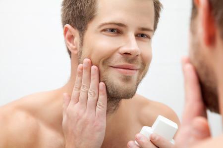 aftershave: Handsome unshaven man looking into the mirror in bathroom
