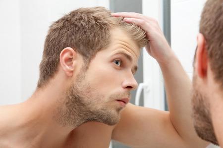 Bel uomo con la barba lunga che esamina lo specchio in bagno