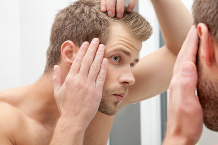 at the mirror: Handsome unshaven man looking into the mirror in bathroom