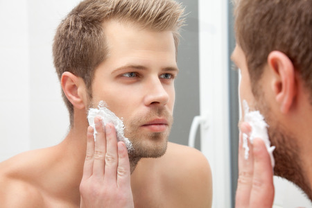 face: Handsome unshaven man looking into the mirror in bathroom