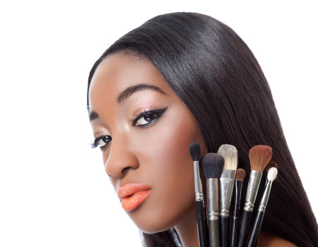 Black woman with straight hair holding makeup brushes isolated on white Standard-Bild