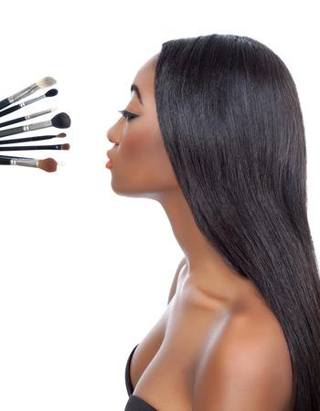 lang haar: Zwarte vrouw met steil haar en make-up borstels geïsoleerd op wit