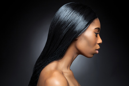 afro hair: Profile of an young black beauty with long straight and shiny hair