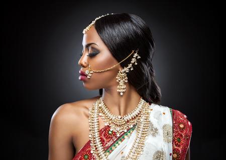 이국적인 인도 신부는 결혼식을 위해 옷을 입고