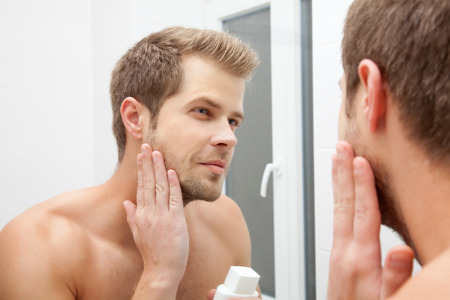 aftershave: Man looking into the mirror and applying aftershave