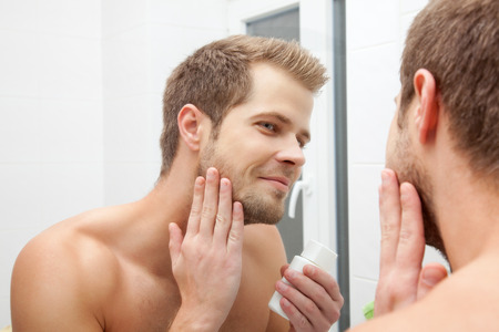 skincare: Man looking into the mirror and applying aftershave