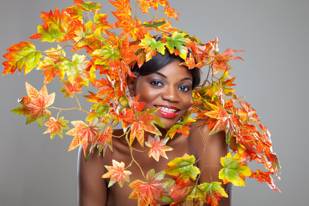 ebony: Beautiful young woman wrapped in autumn leafs