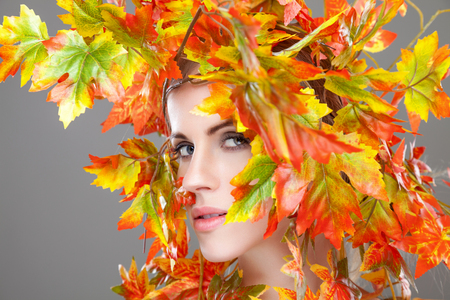 autumn leafs: Beautiful young woman wrapped in autumn leafs