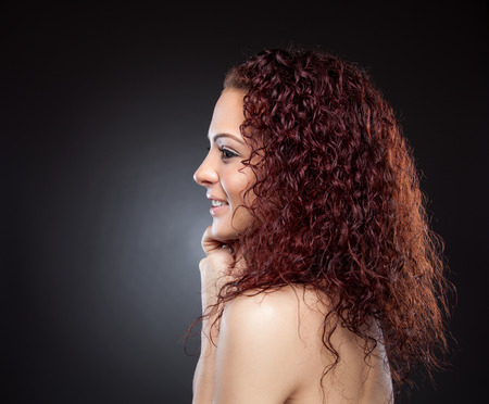 rood haar: Profile view of a beautiful woman with curly red hair