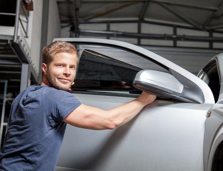 La aplicación de la hoja de tintado en una ventanilla del coche en un taller