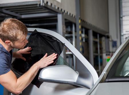 garage automobile: L'application de la feuille de teinture sur une fenêtre de la voiture à un atelier