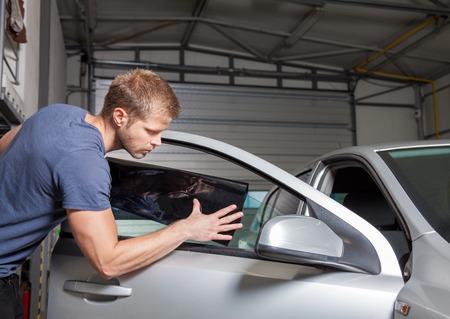 VENTANAS: La aplicación de la hoja de tintado en una ventanilla del coche en un taller