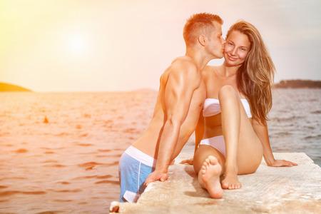 hombres besandose: Joven feliz y rom�ntica pareja se besa en una playa durante la puesta del sol Foto de archivo