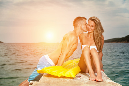 romantic beach: Young happy and romantic couple kiss on a beach during sunset