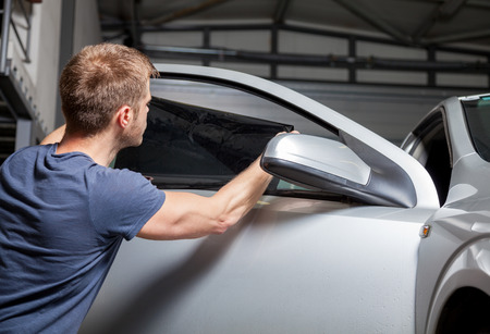 mecanico automotriz: La aplicaci�n de la hoja de tintado en una ventanilla del coche en un garaje