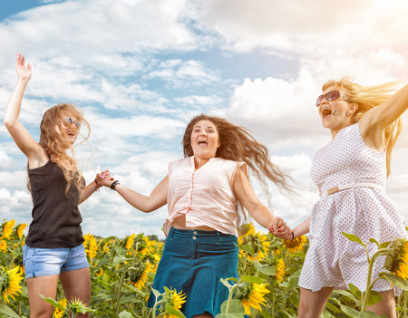 Group of friends having fun outdoors in a field Stock Photo