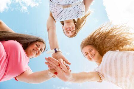 mujeres felices: Tres mejores amigos mirando hacia abajo y de la mano oudoors