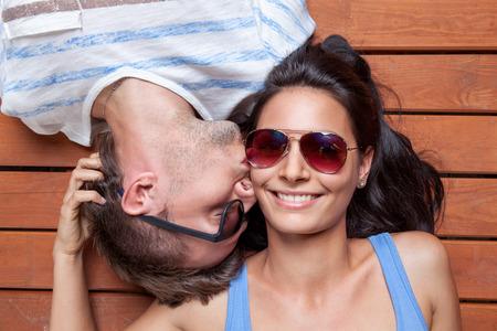 gafas de sol: feliz pareja de jóvenes cabeza a cabeza tumbado en un suelo de madera Foto de archivo