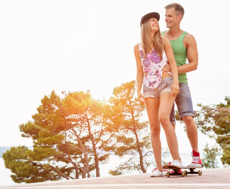 oudoors: Young happy couple oudoors with a skateboard Stock Photo