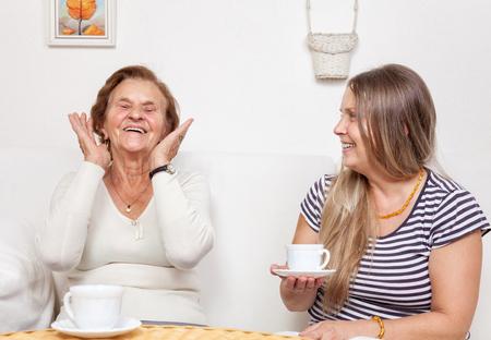 abuela: Cuidador tomando una taza de té con una mujer jubilada de edad avanzada
