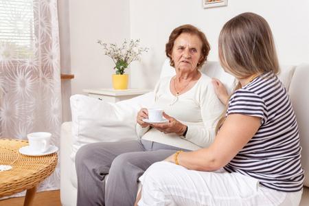 abuela: Cuidador tomando una taza de t� con una mujer jubilada de edad avanzada