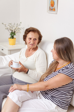 elderly people: Carer having a cup of tea with an elderly retired woman
