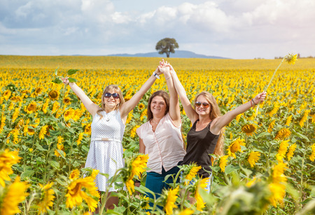people laughing: Three young friends having fun in a sunflower field Stock Photo