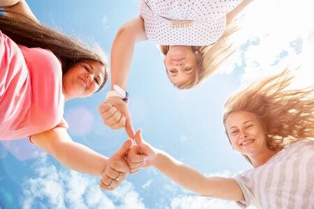 oudoors: Young and happy friends oudoors looking donw Stock Photo