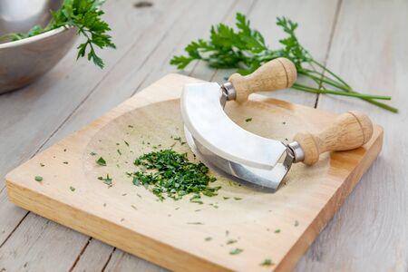 garnish: Freshly chopped parsley on a board with mezzaluna