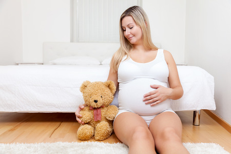 Young pregnant woman sitting on the floor next to a teddy bear