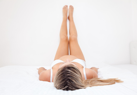 Pregnant woman lying on bed with legs raised up